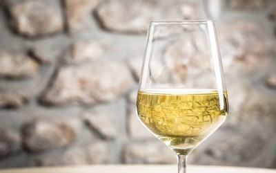 White wine glass in restaurant with copy space for text.
